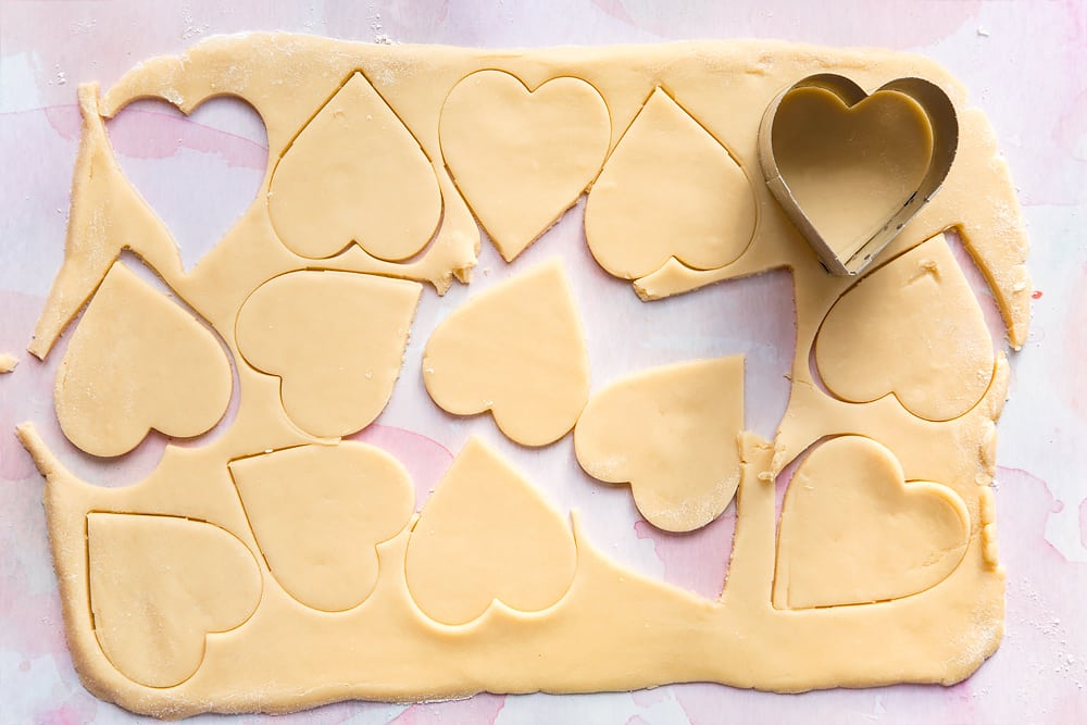Overhead shot of rolled out cookie dough with heart cutouts