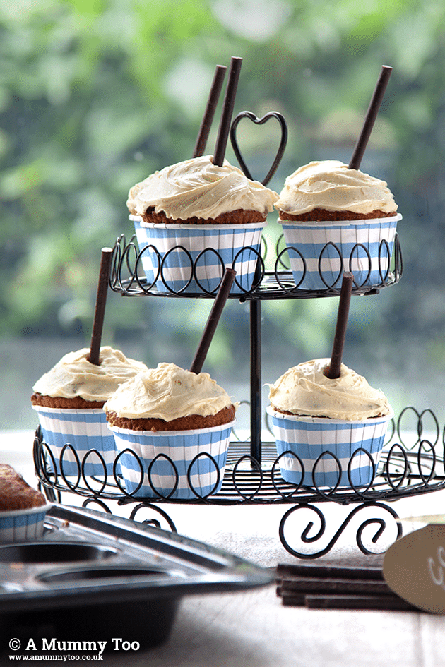 Banana cupcakes topped with clotted cream, shown in a tiered cupcake stand
