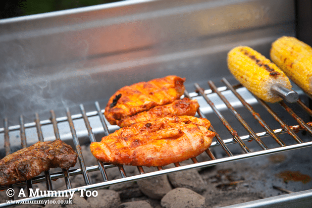 Chicken cooking on a BBQ grill alongside sweetcorn