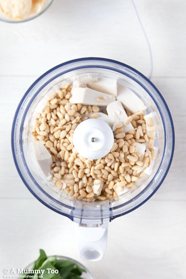Blending ingredients in a food processor to make this pesto dip