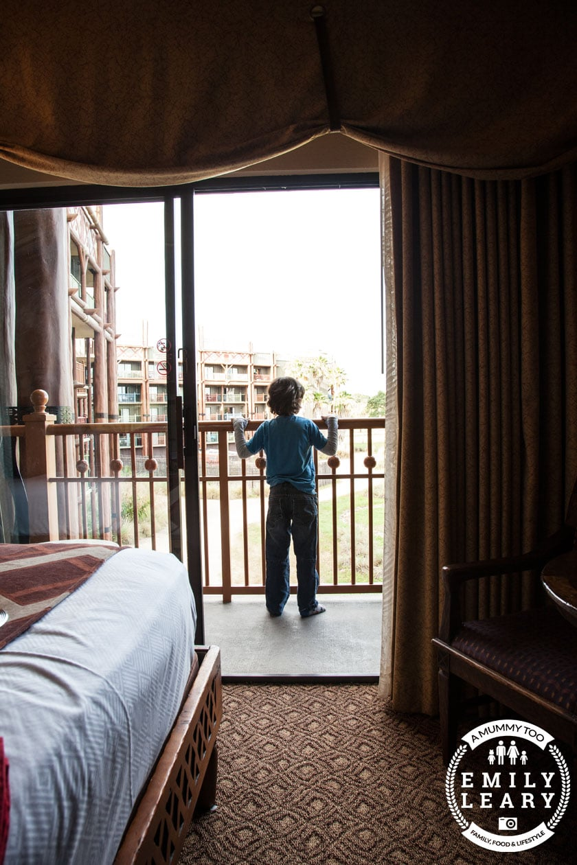 front angle shot of a boy looking over the Walt Disney World Florida Animal Kingdom Lodge balcony with a mummy too logo in the lower-right corner