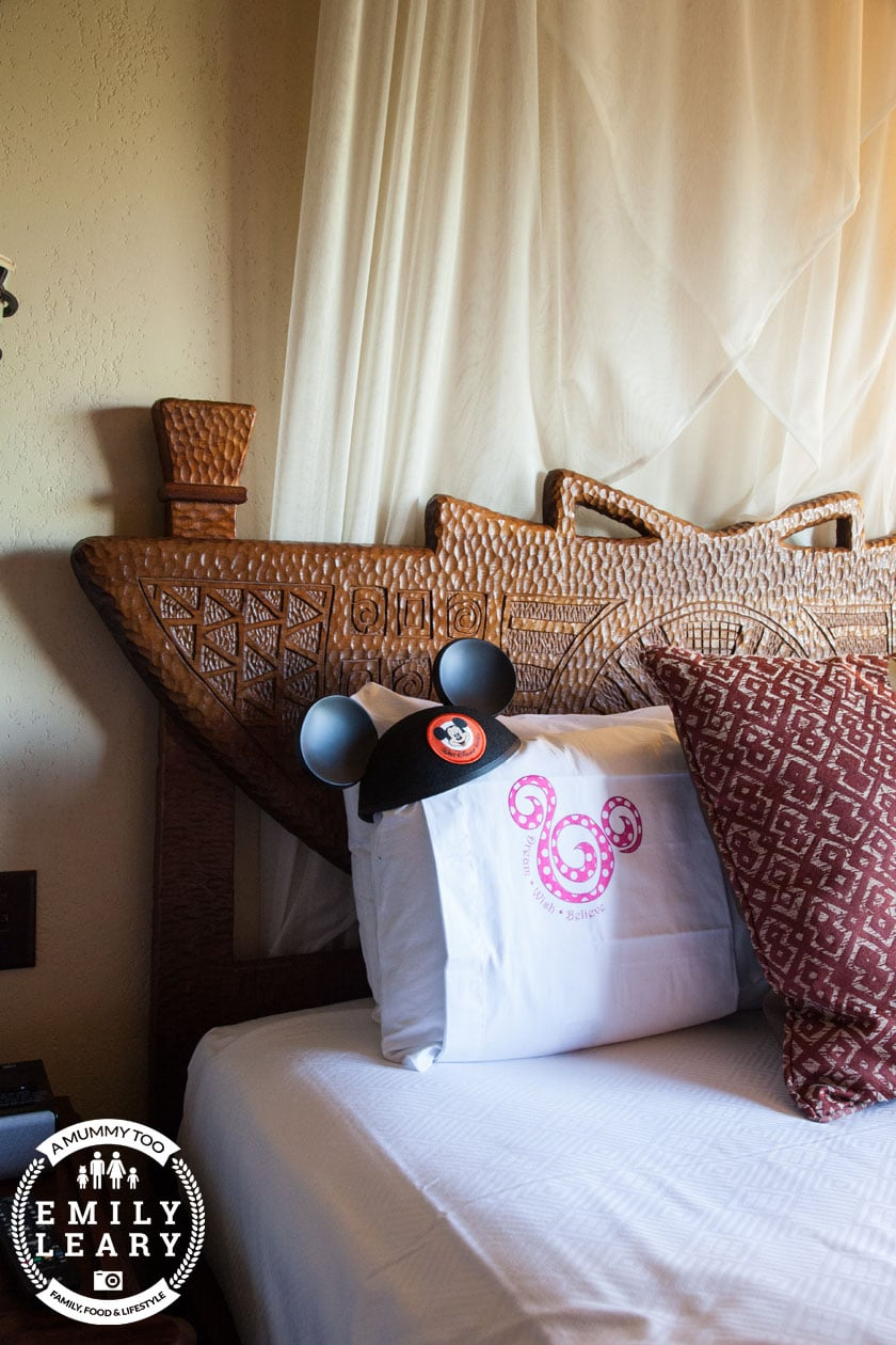 side angle shot of Animal Kingdom Lodge bed with pillows with a mummy too logo in the lower-left corner