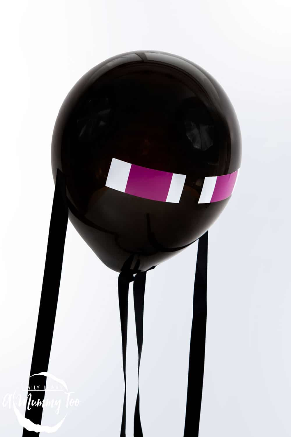 Front angle shot of a black Enderman minecraft balloon with amummytoo logo in the lower-left corner