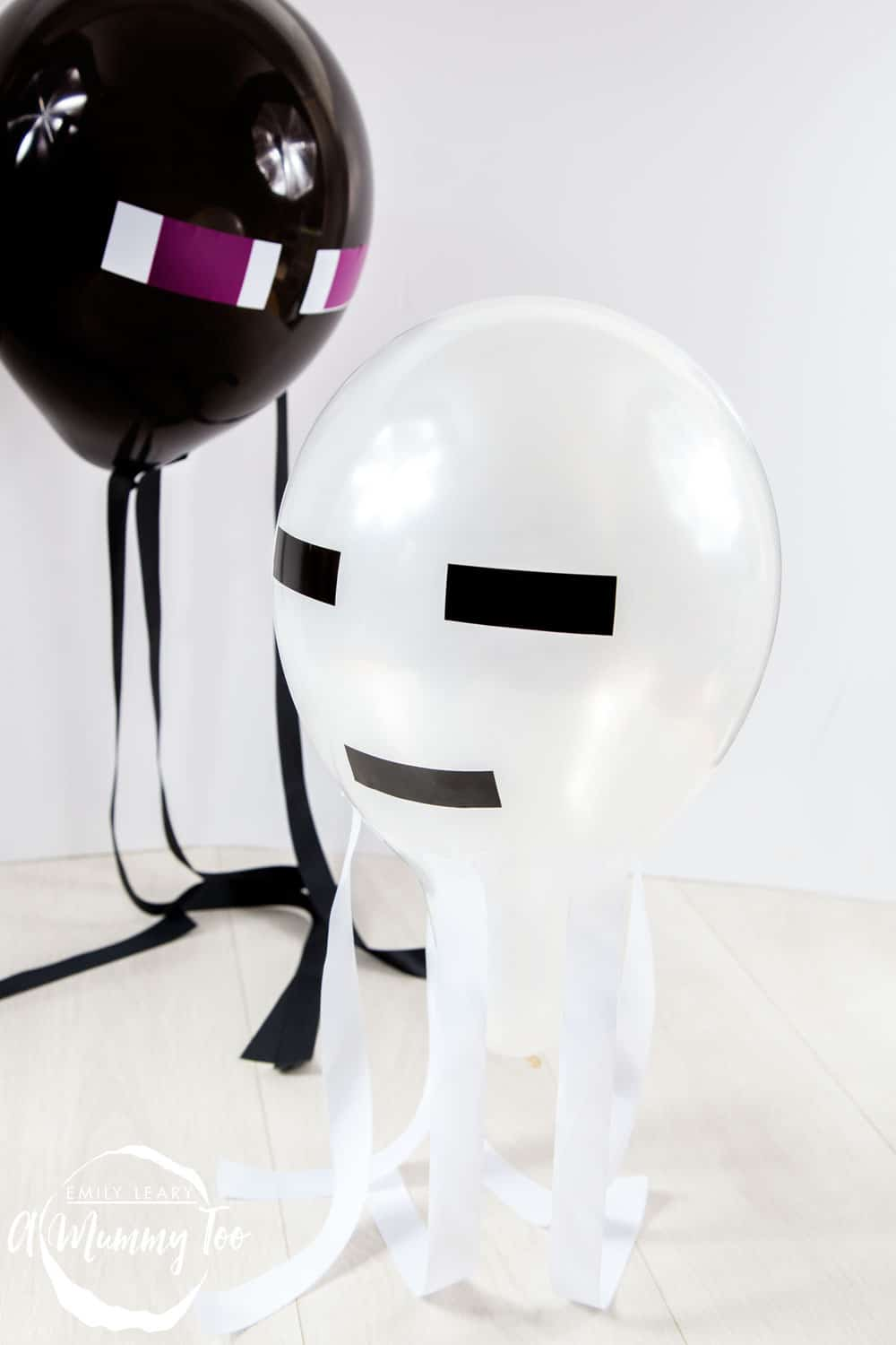 Front angle shot of black and white minecraft balloons with amummytoo logo in the lower-left corner
