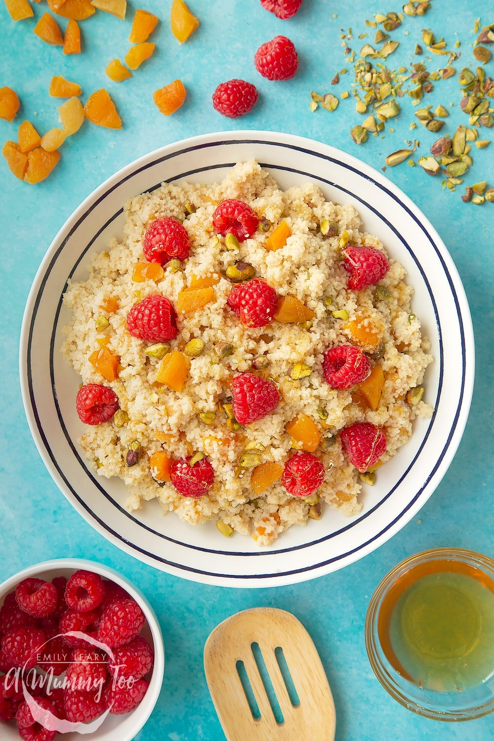 Overhead shot of the sweet breakfast couscous in a white bowl with black decoation. At the side of the bowl there's some of the ingredients required for the recipe.
