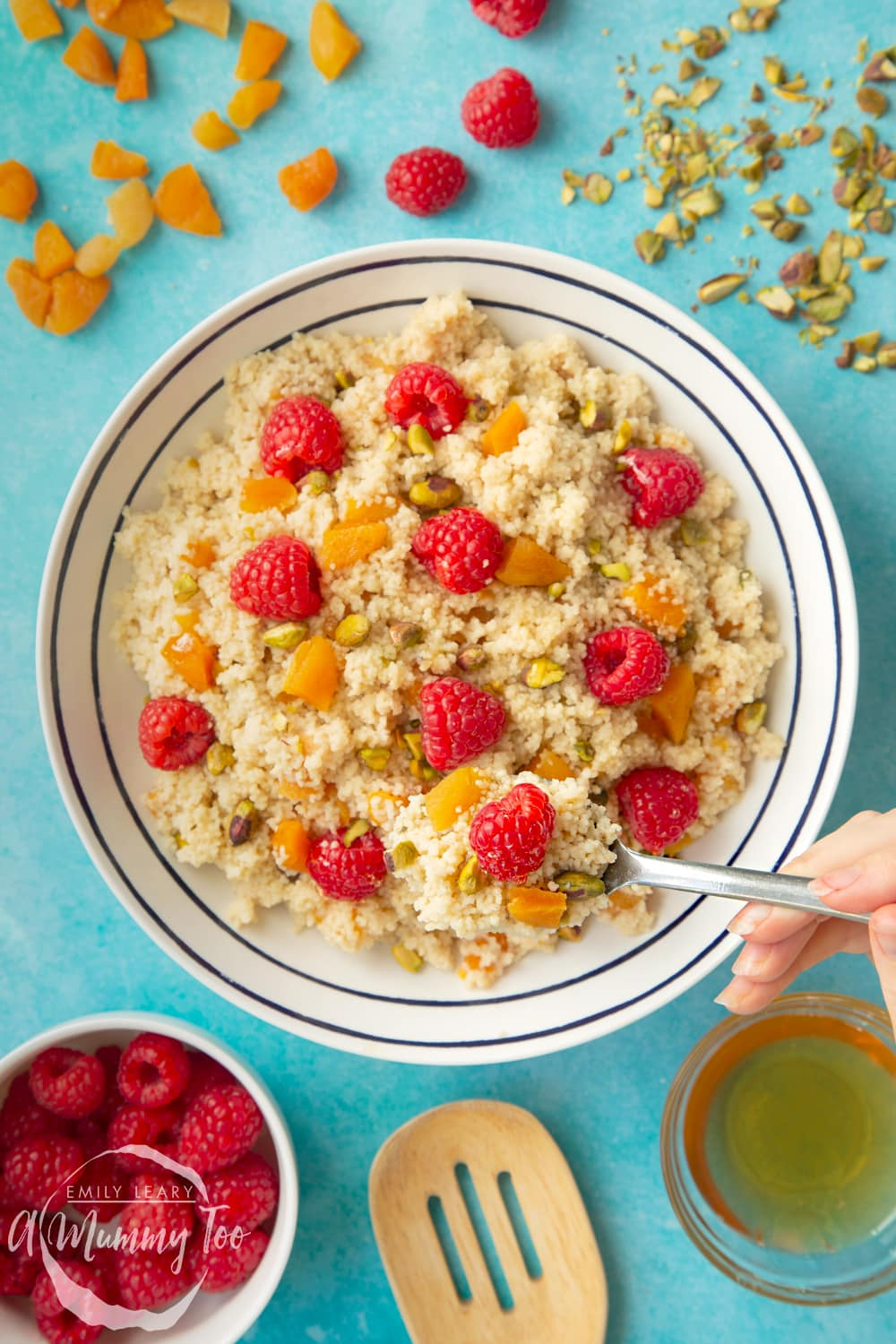 Overhead shot of a spoon going into the bowl of sweet breakfast couscous. The bowl is surrounded by ingredients required for the recipe.