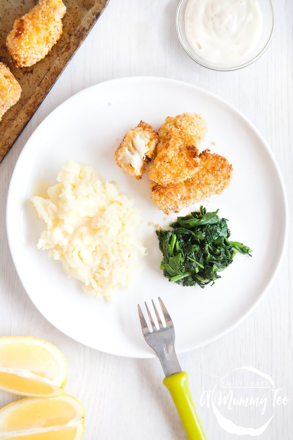 Homemade fish fingers served with spinach and mashed potato