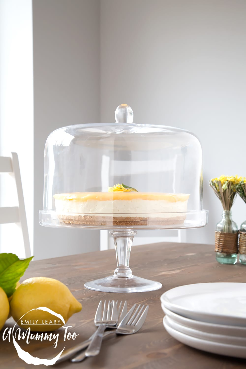 No-bake lemon curd and white chocolate cheesecake in a glass stand on a wooden table.