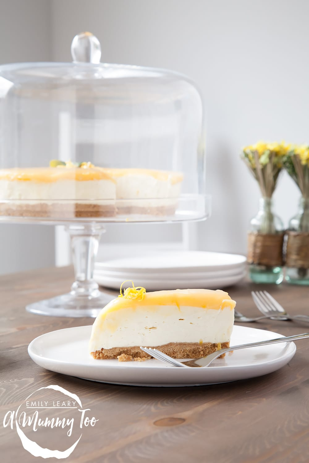 A slice of no-bake lemon curd and white chocolate cheesecake on a plate, with the remaining cheesecake in a stand behind.