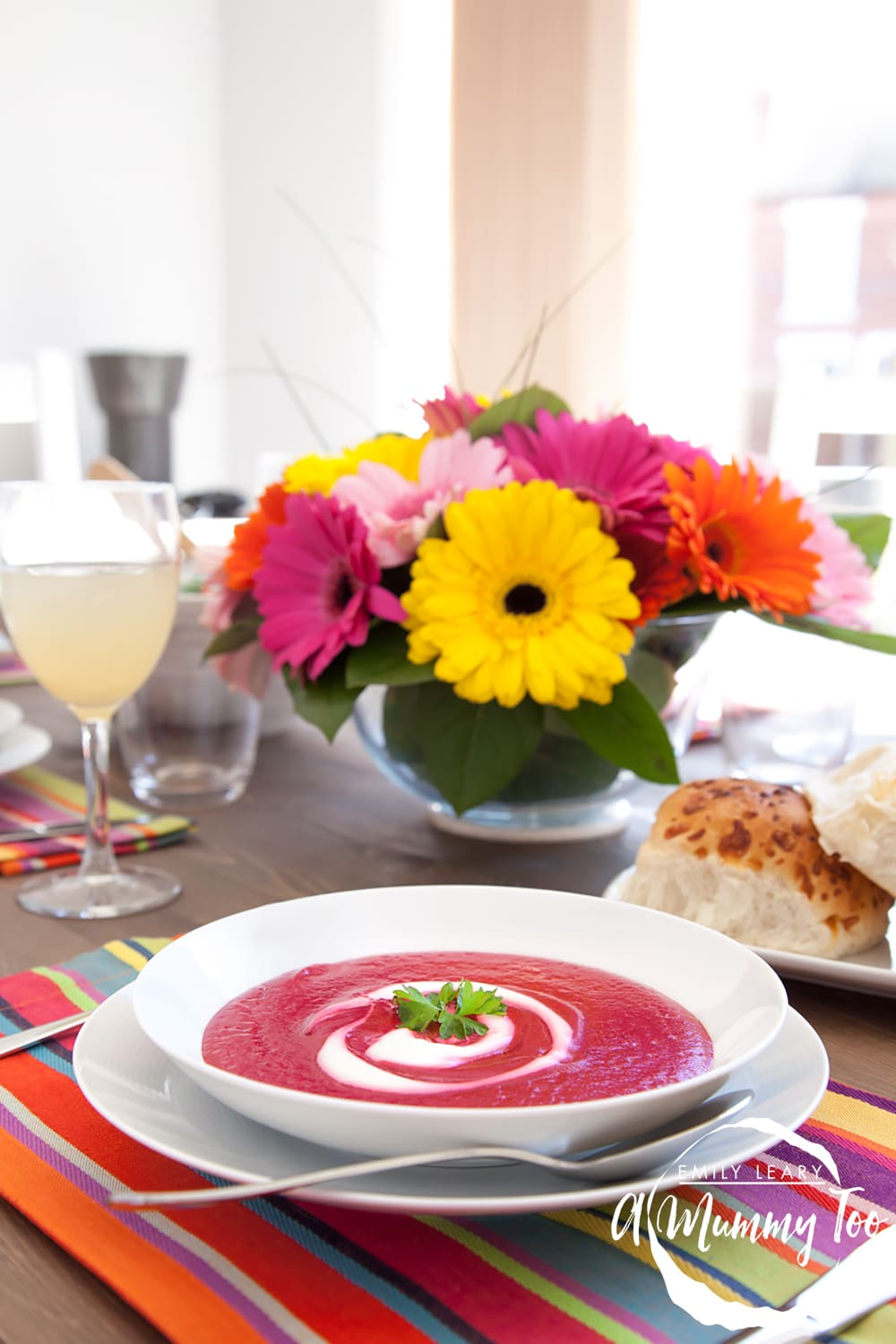 Vibrant pink roasted beetroot soup served in a shallow white bowl on a table set for dinner.