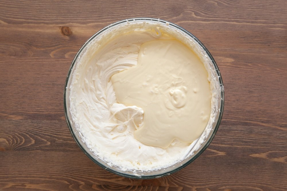 A bowl containing cream cheese, double cream, vanilla and sugar beaten together, topped with melted white chocolate.