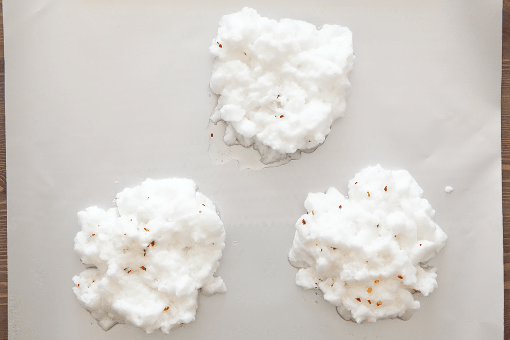 The whites for spicy eggs in clouds spread in three piles on a baking tray.