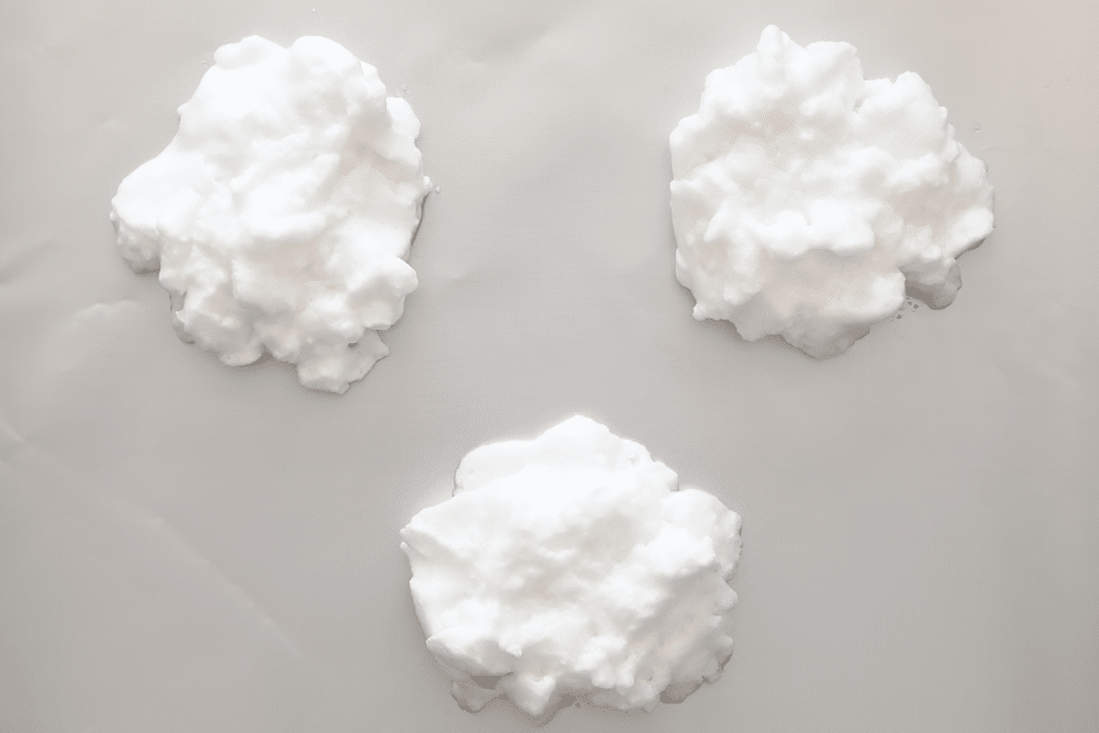 Egg clouds using whipped egg whites, in three piles on a baking sheet.