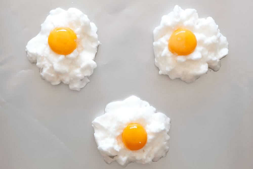 Toppin the eggs in clouds with an egg yolk to create eggs in clouds