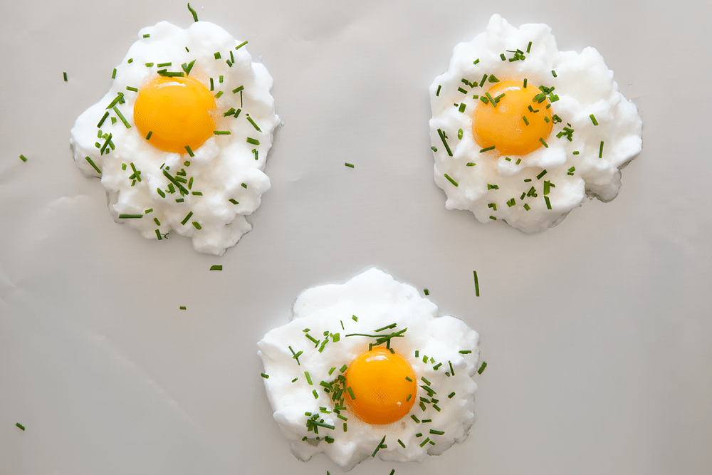 Eggs in clouds sprinkled with chives on a baking tray - ready to bake.