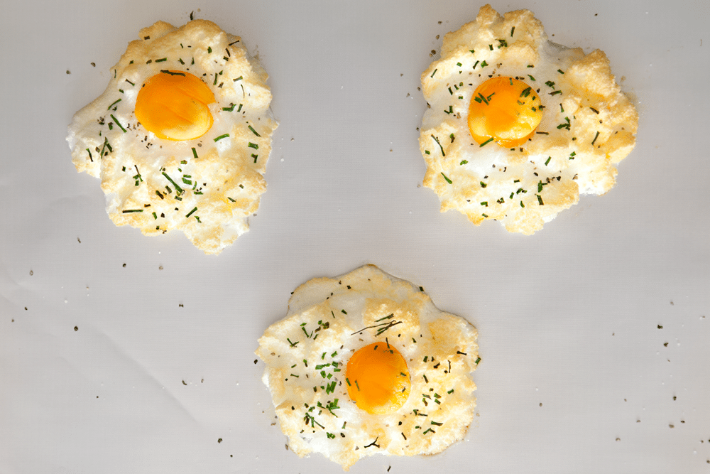 Freshly baked eggs in clouds with chives