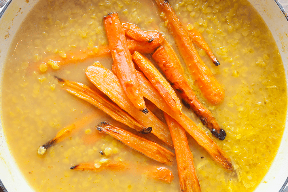 Roasted carrots are added to the pot
