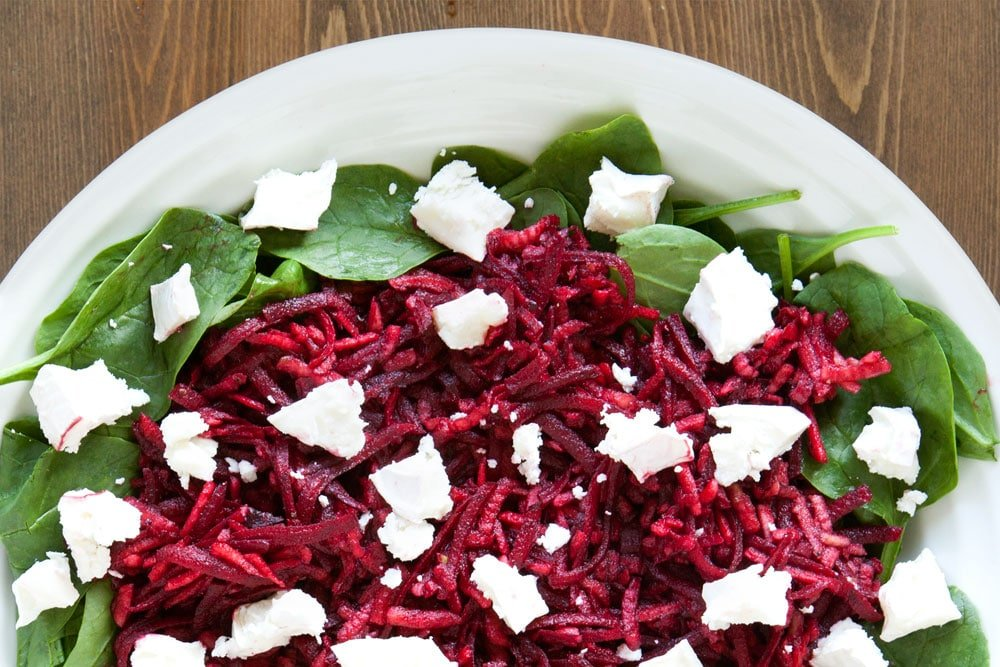 Dressing the apple and beetroot salad with goat's cheese