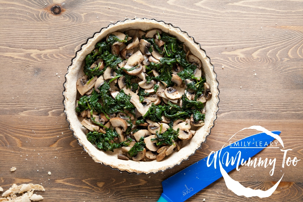 The spinach and mushroom mix is added to the quiche