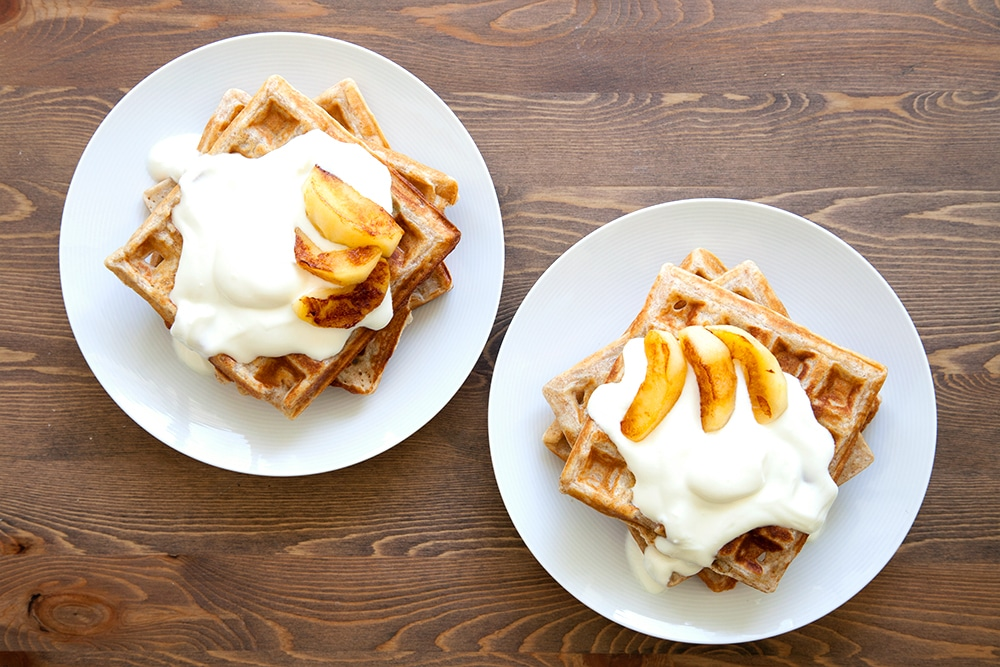 Serve your granola waffles stacked and topped with natural yogurt and sliced apple