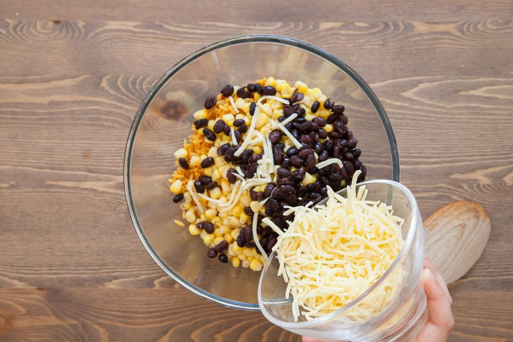 Mixing in the taco ingredients, adding grated cheese