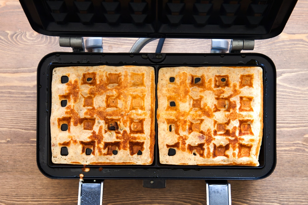 Cooking the granola waffles in a waffle maker until golden