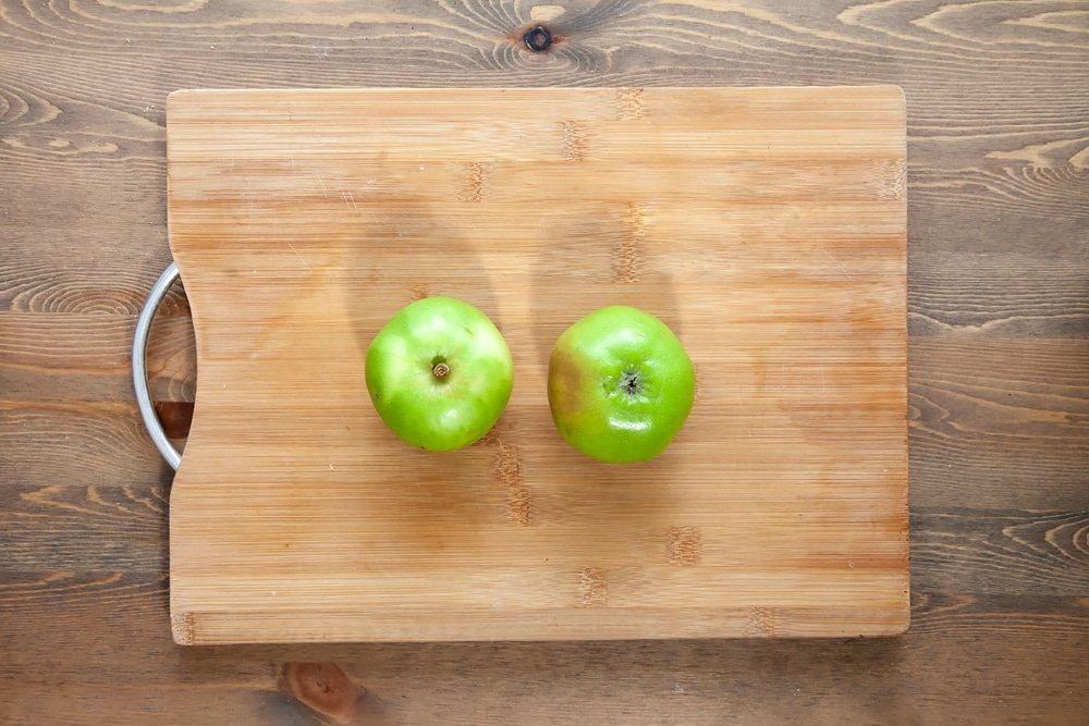 Two bramley apples on a chopping board