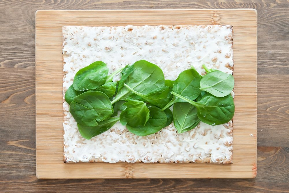Assembling the spicy quinoa and bean protein wrap, starting with a layer of spinach