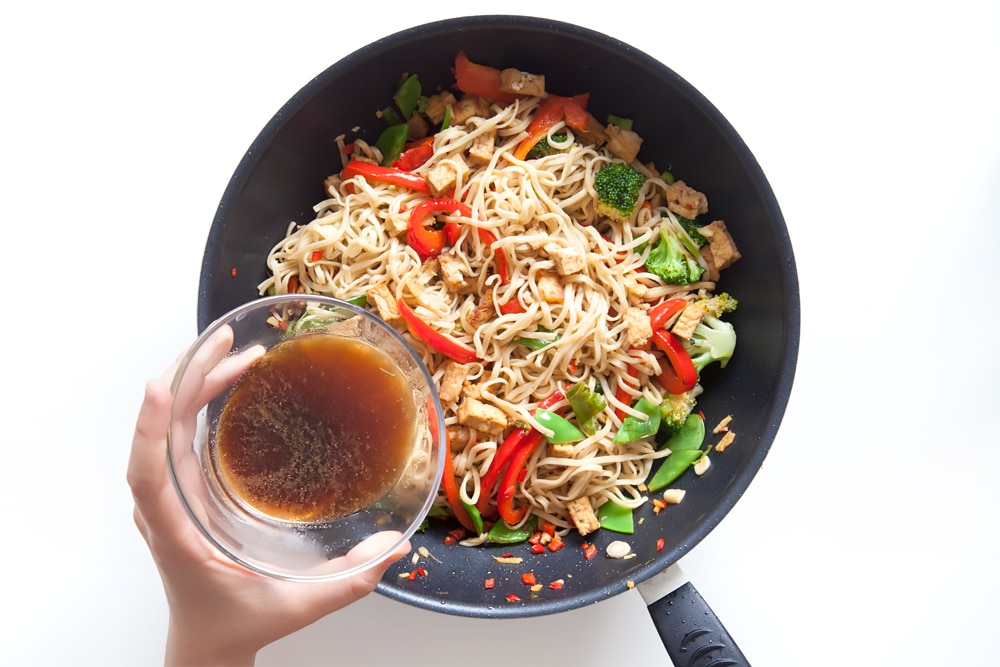 Pouring the Coca-Cola Zero Sugar sauce over the tofu and vegetable noodle stir fry