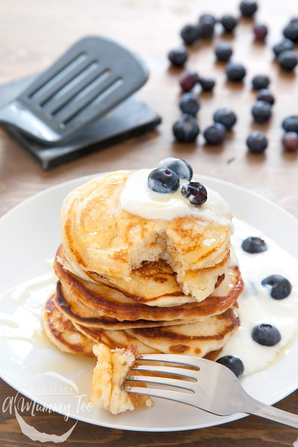 Beautifully fluffy coconut yogurt pancakes, topped with blueberries