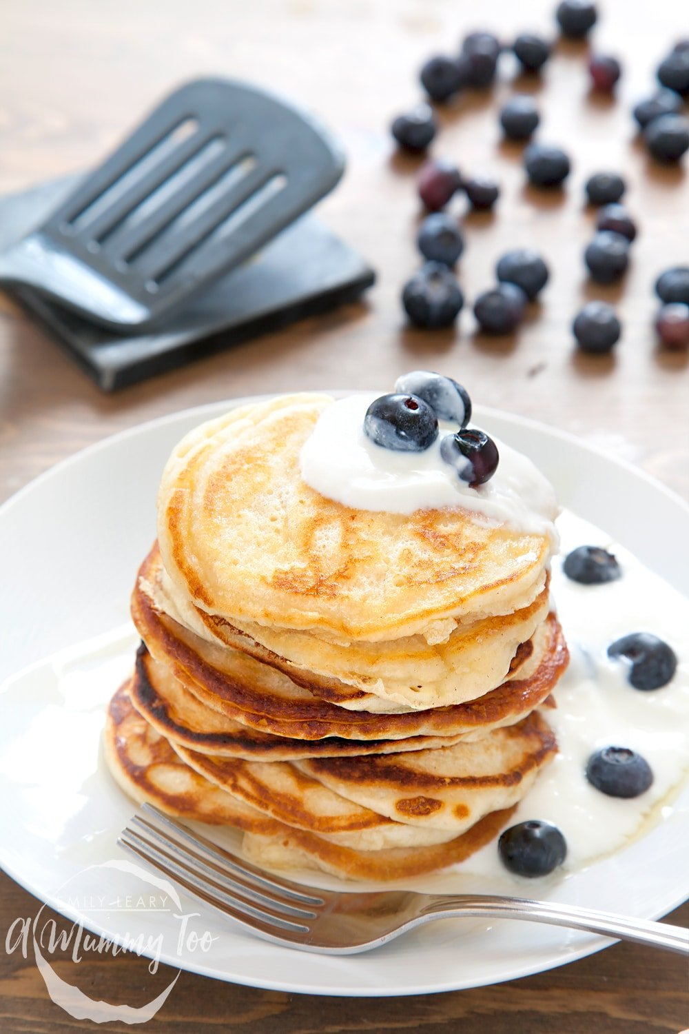 A stack of coconut yogurt pancakes, topped with coconut yogurt and blueberries