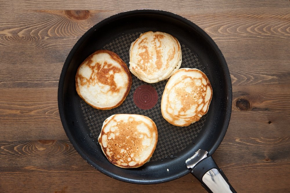 Frying the coconut yogurt pancakes until golden