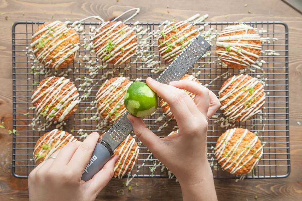 Grating lime zest over the lime and white chocolate muffins