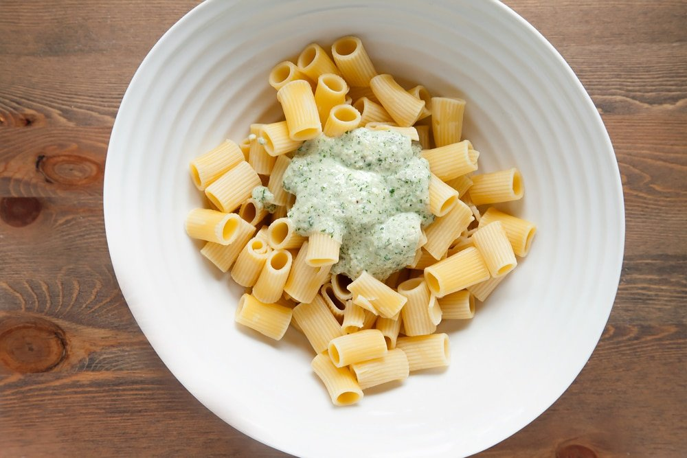 Topping the rigatoni with freshly made pesto