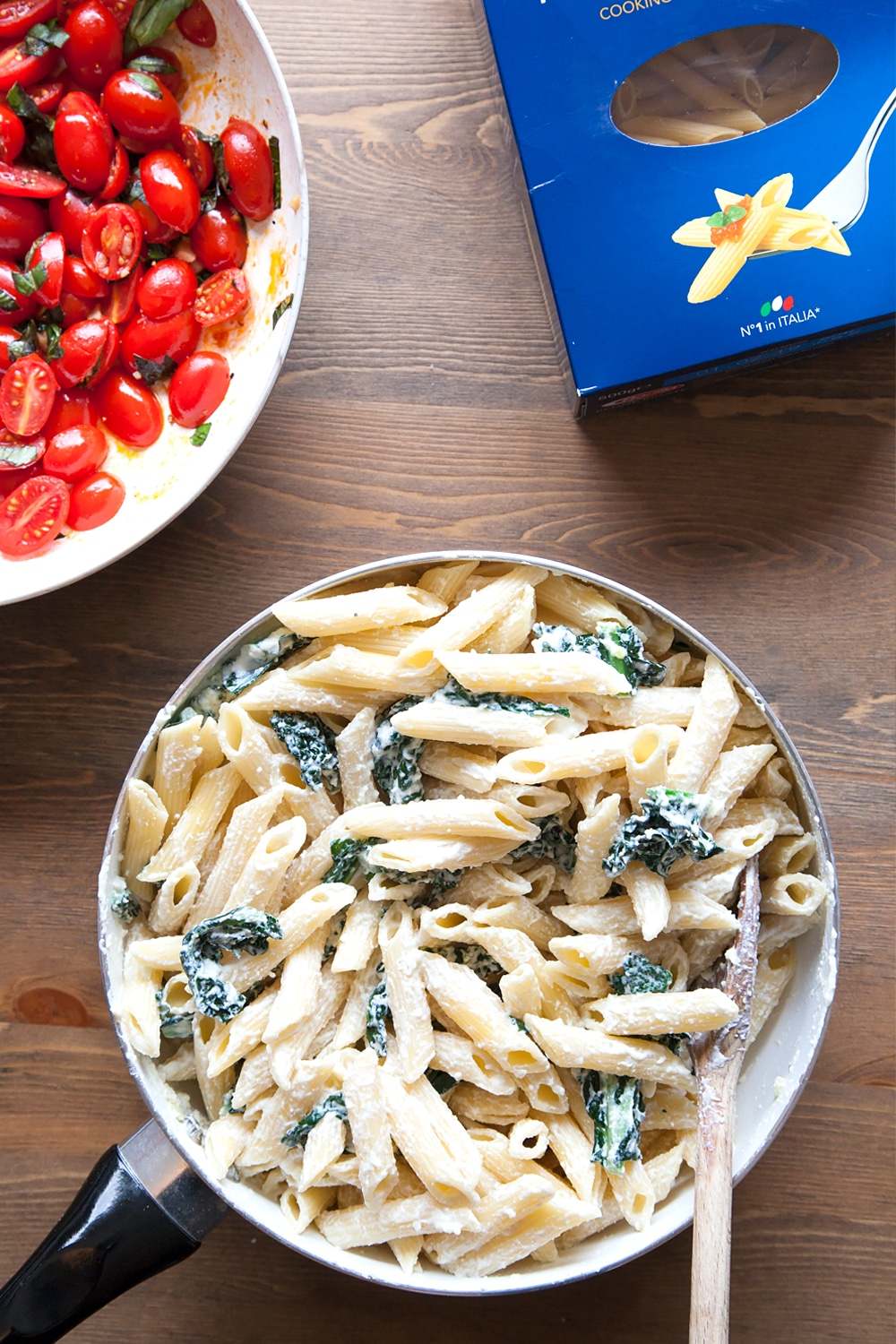 Freshly cooked penne pasta is added to the frying pan