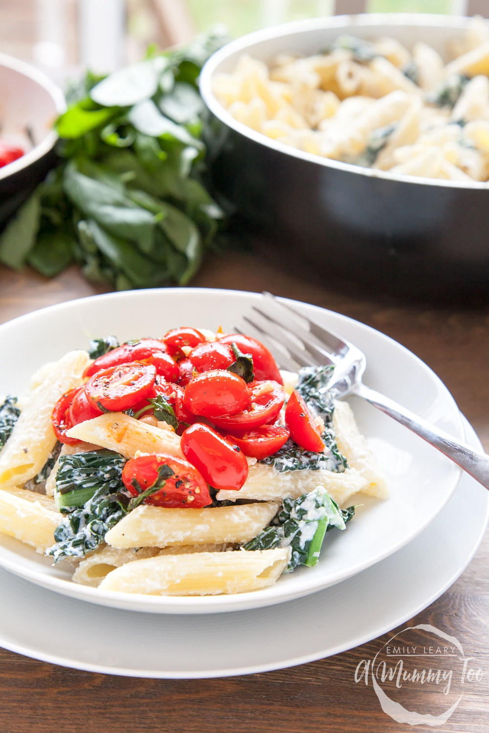 The cavolo nero penne with basil fried tomatoes is served, topped with more basil fried tomatoes