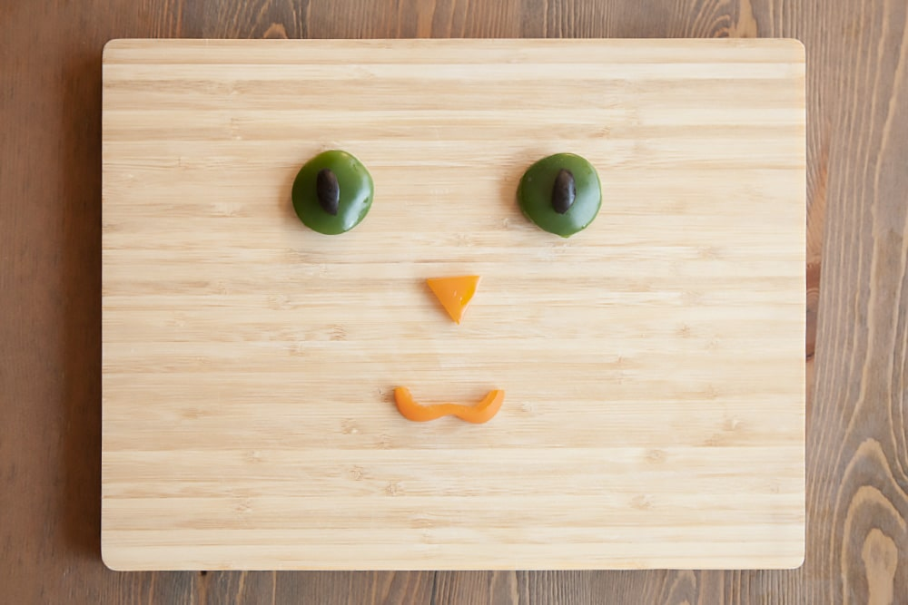 Create the kitty face using your selection of toppings - here we've used vegetables