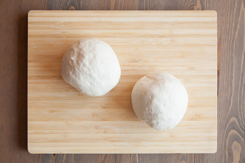 The pizza dough is separated into two balls