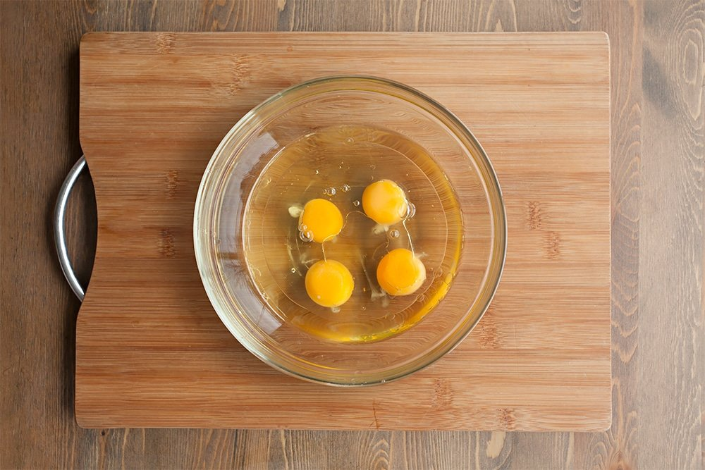 Mixing eggs and oil together in a glass bowl