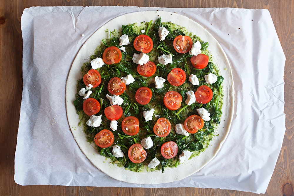 Assembling the gluten-free spinach and goat's cheese pesto tart - top the pesto with spinach, cherry tomatoes and crumbled goat's cheese