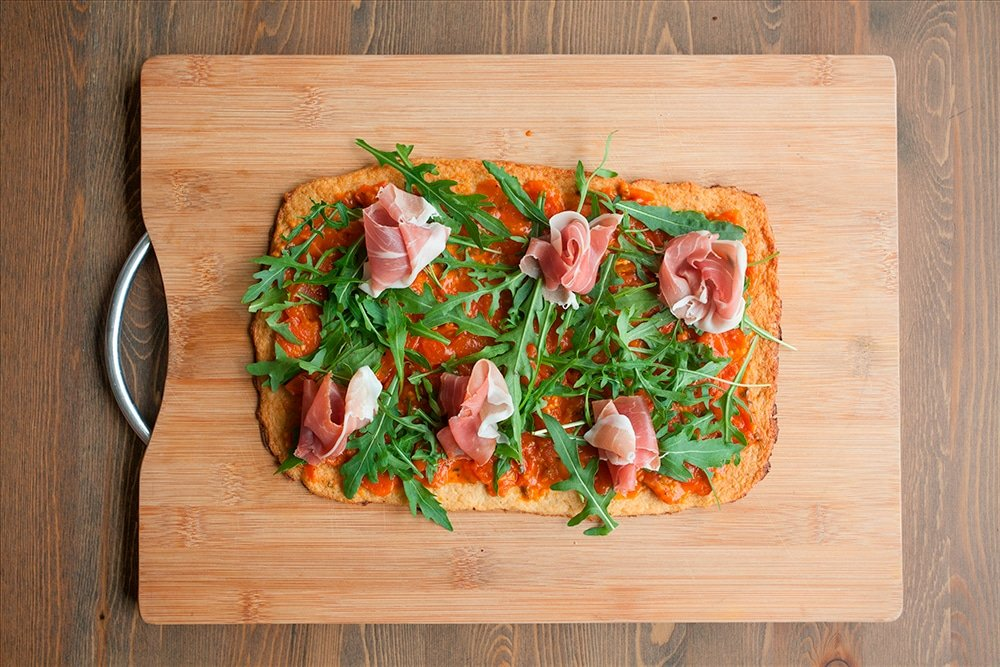 Prosciutto is added to the cauliflower crust pizza