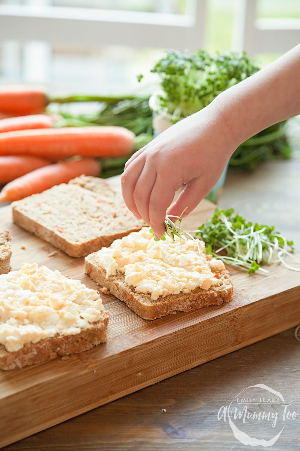 Sprinkling the home-grown cress onto the egg mayo sandwich filling