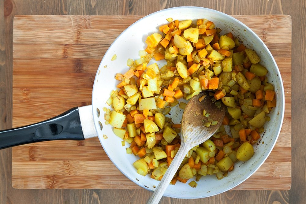 Cooking the chopped vegetables in a frying pan, one of the first steps in creating this tasty carrot and mango curry