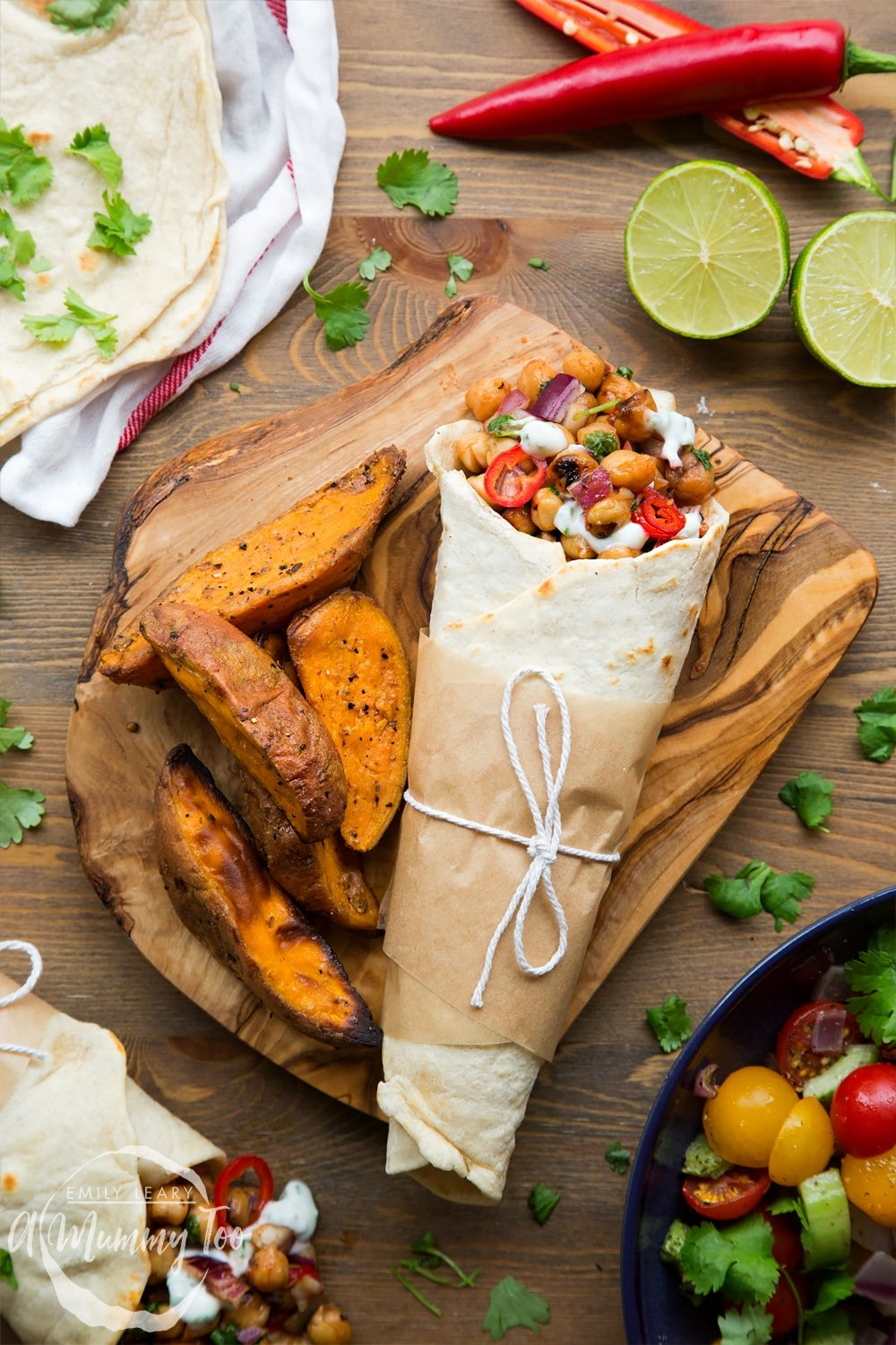 Summer BBQ chickpea wraps, shown at a BBQ ready to eat, alongside potato wedges, tortillas, limes, chilli