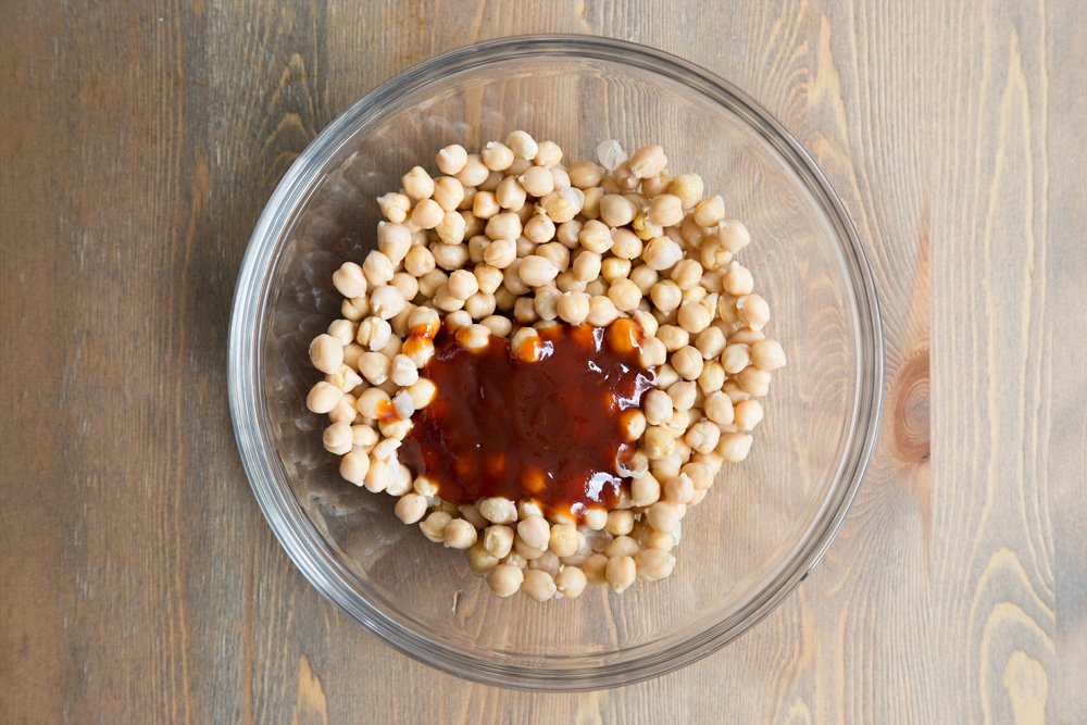 BBQ sauce shown on top of chickpeas, ready to be mixed in to add flavour
