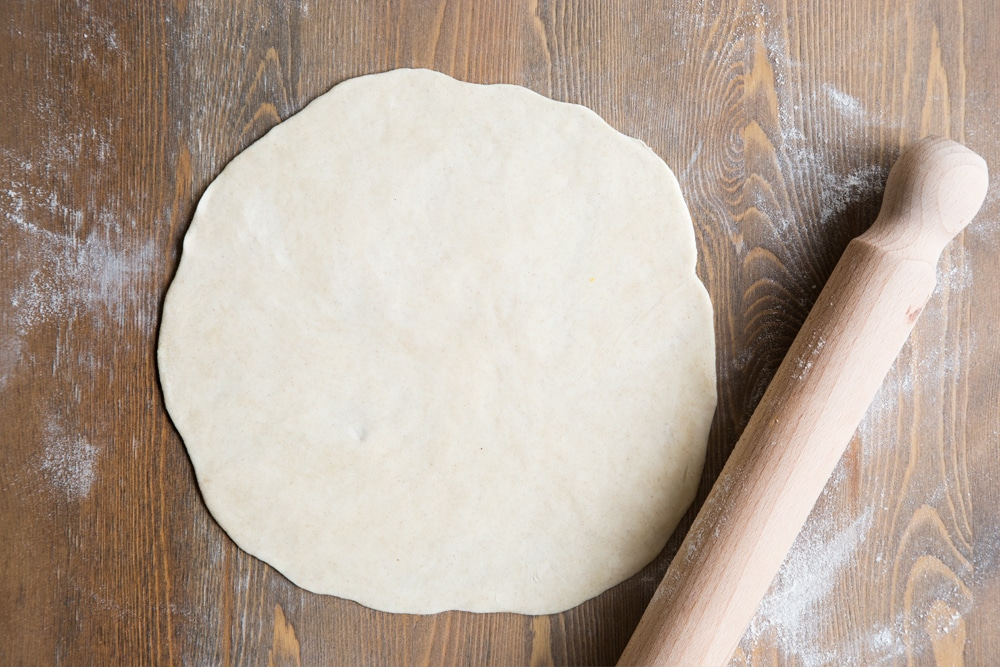 Tortilla dough rolled out flat into a circle, shown alongside a rolling pin