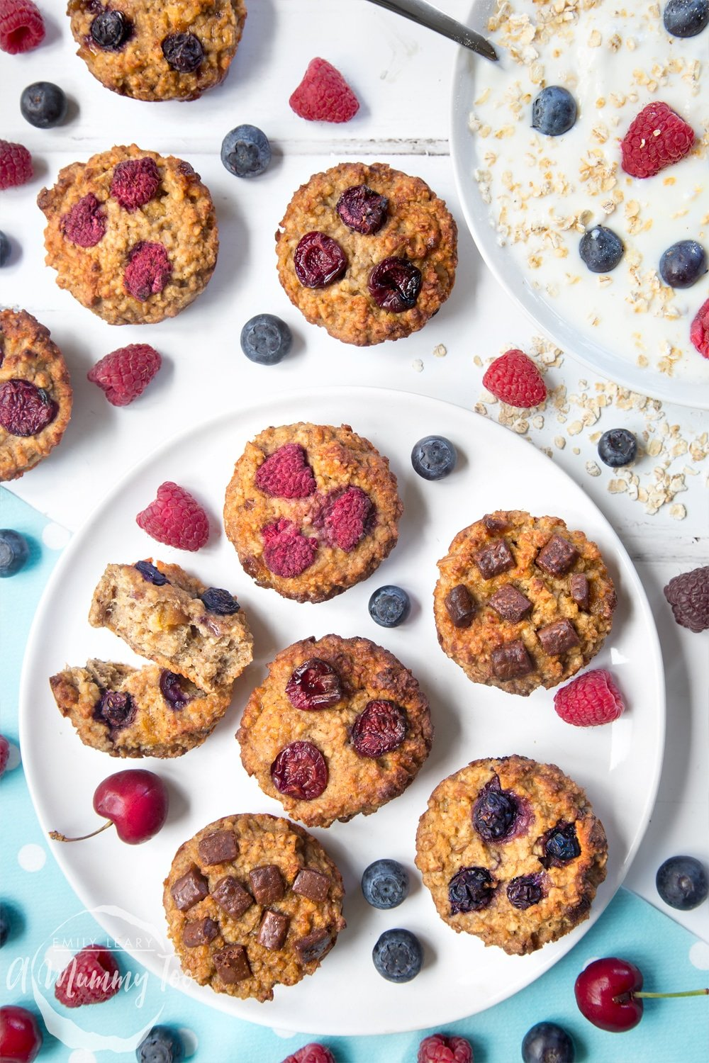 Yoghurty summer fruit breakfast muffins surrounded by raspberries, blueberries and yoghurt. Find out how to make this delicious, healthier breakfast treat in my recipe!