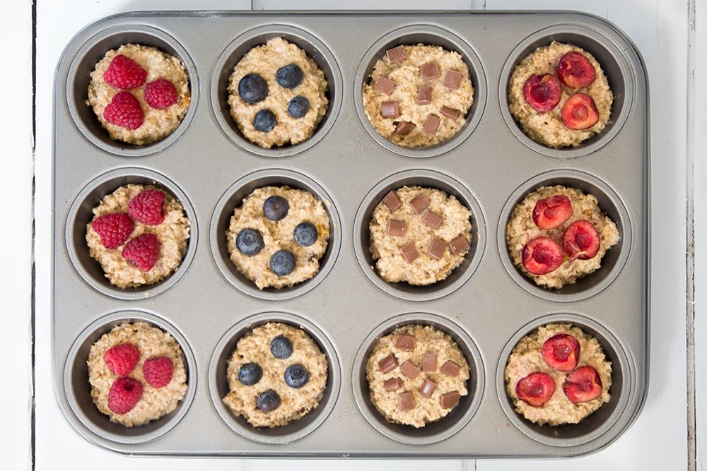 The yogurty breakfast muffins are ready to bake! Shown here topped with raspberries, blueberries and chocolate chips