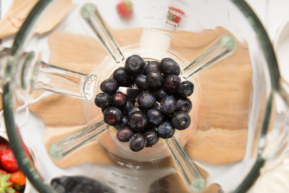 Blueberries shown inside a blender, part of this quick and simple fruit and yogurt lollies recipe