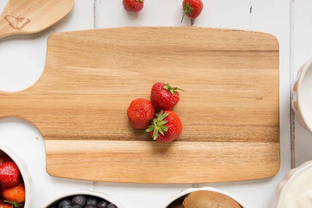 Strawberries, one of the main ingredients in this fruit yogurt lolly, shown on a chopping board